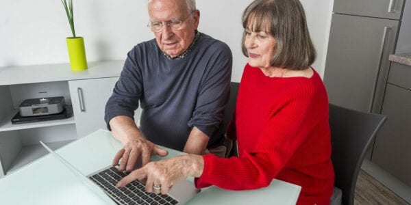 An elderly man and woman point at a laptop as they shop online at home, demonstrating the importance of age inclusive digital marketing