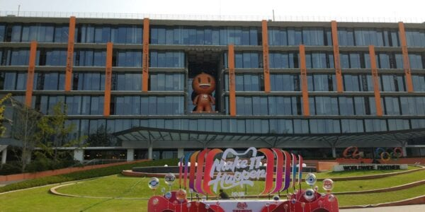 Image of Alibaba's campus in Beijing. A glass building with the mascot in the middle and a slogan 'make it happen' at the forefront of the image.