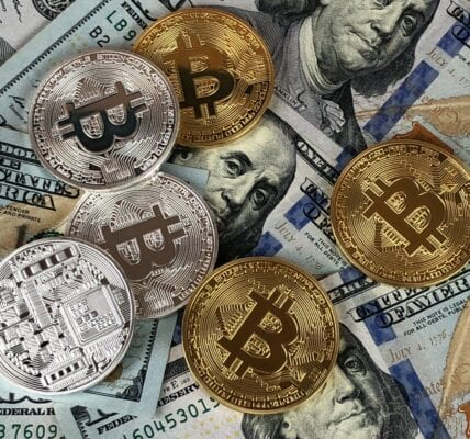 Bitcoin Cryptocurrency coins scattered across some US dollar Hundred dollar bills