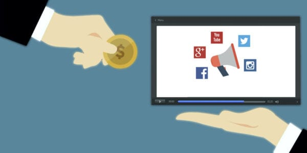 Image of megaphone and social media icons inside computer screen next to hand holding a coin