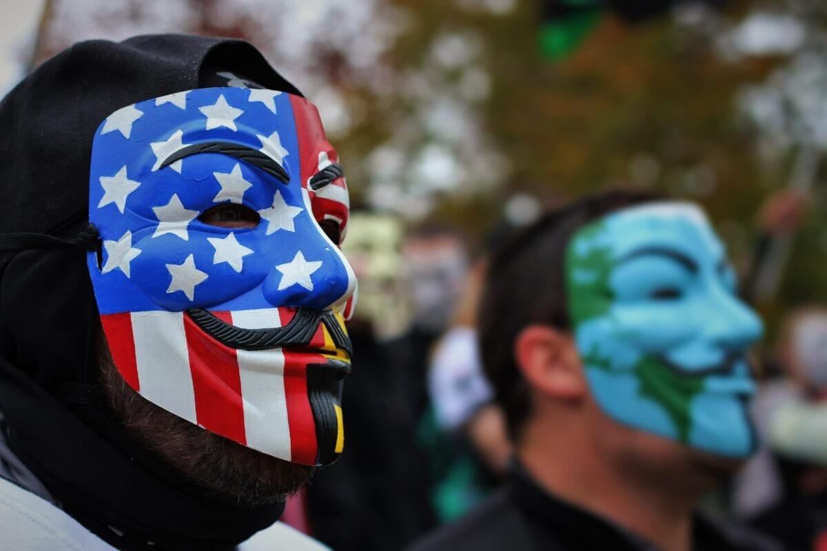 Protesters with anonymous masks look into the distance.