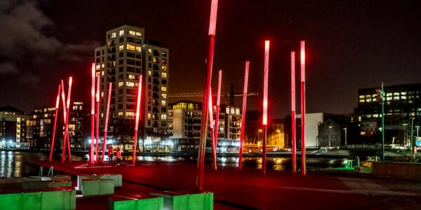The red glowing angled light sticks of Grand Canal Square in Dublin Docklands at night, surrounded by green, polygon-shaped planters. High-rise buildings with lights turned on, can be seen in the background