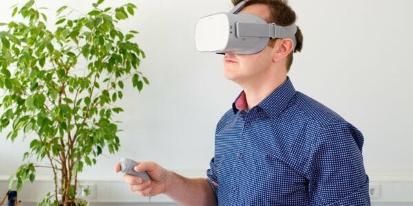 A man with a virtual reality headset and a plant behind him