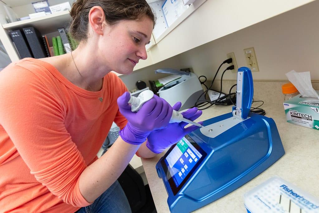 A women using a DNA testing machine in a laboratory