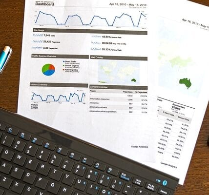 A Keyboard, a pen and some papers with business figures on it lying on a table