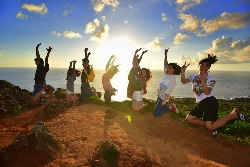 A group jumping in celebration after winning the Instagram competition on a cliff while the sun sets over the sea.