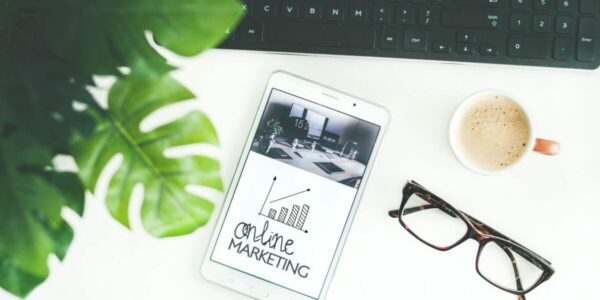 """Image of a phone on a desk with """"Online Marketing"""" written on the phone. Organic Reach is one element of online marketing."""