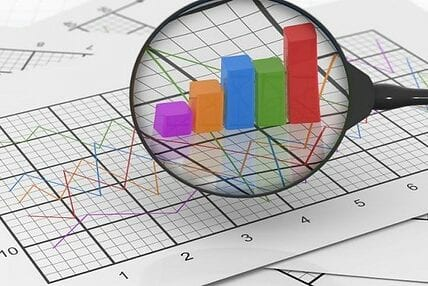 Image of magnifying glass showing data analytics on a page
