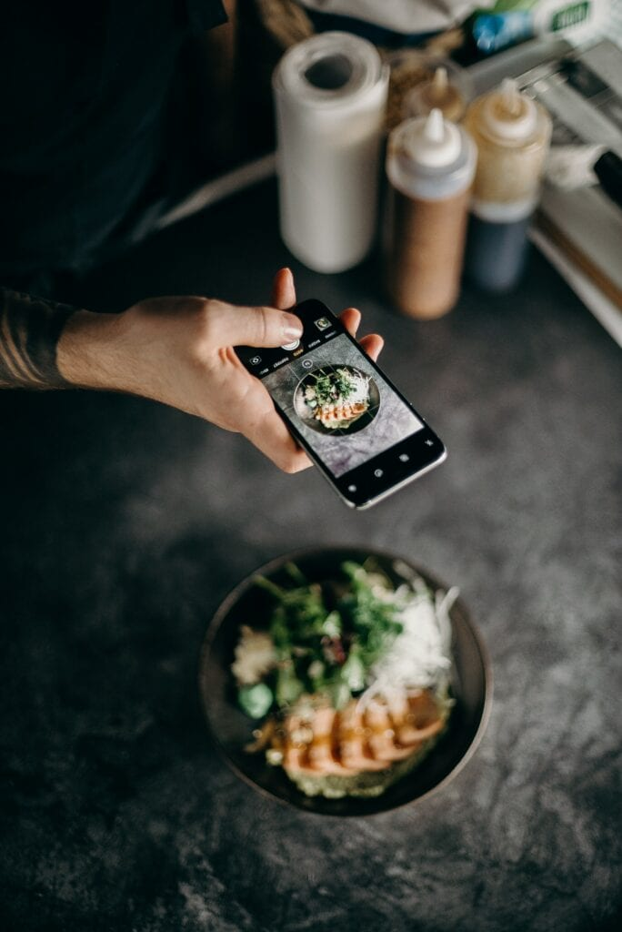 Image of a Food Influencer taking pictures of a dish with an iPhone