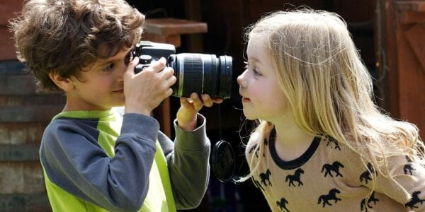 Image of young child using a camera to take a photo of another child, on a sunny day.