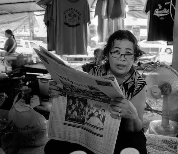 Image of a lady reading a newspaper with a lot of advertisements, a form of traditional marketing.