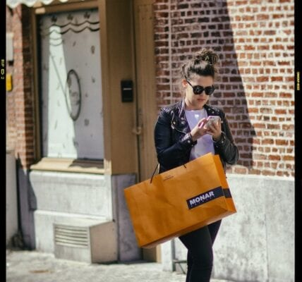 This image is of a person walking down the street with an orange shopping bag on their arm. They are holding their phone in both hands and looking down at it. They are wearing black jeans, a white top, a black leather jacket, sunglasses, and have their hair up in a bun.