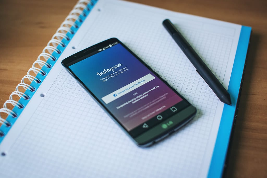 A phone on a desk on top of a notebook. The Instagram log-in page is open on the phone. There is a pen located to the right of the phone.