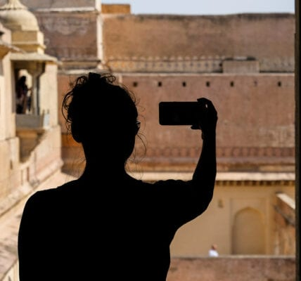 A woman taking a selfie on her smart phone.